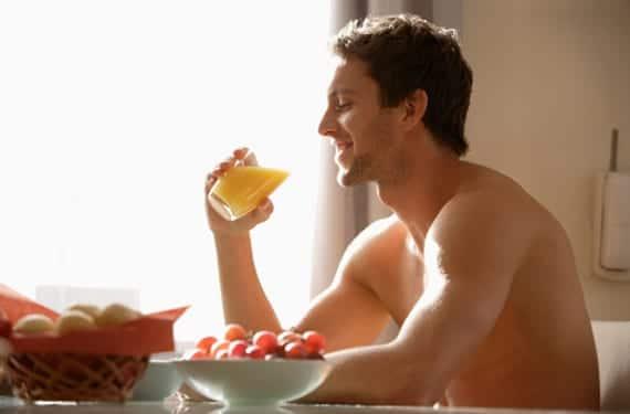 Hombre joven bebiendo zumo de naranja