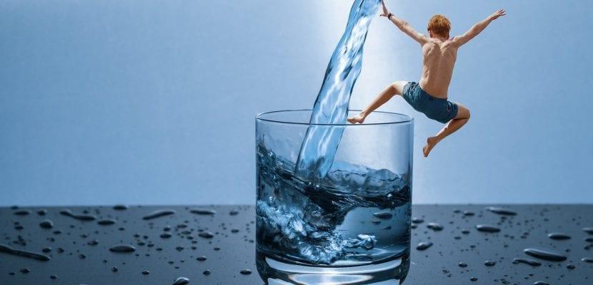 niño saltando a un vaso de agua